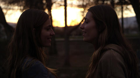 Twin teenage girls face to face at sunset Live Action