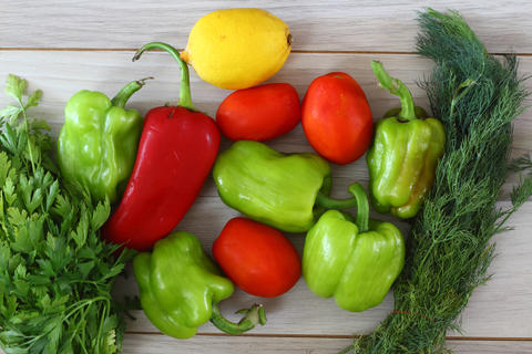 Red pepper, green pepper, tomato, parsley, dill, lemon on a brown wooden background top view, fresh フォト