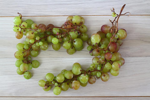 green grapes with leaves on a old wooden background. Top view , copy space フォト