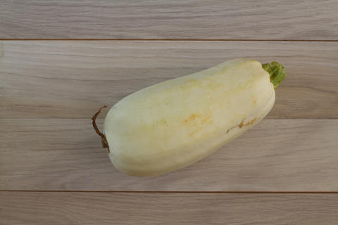 Fresh organic zucchini on the white wooden table. Fresh squash with copy space フォト