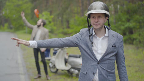 Adult Caucasian man in formal suit and motorcycle helmet hitchhiking as blurred Live Action