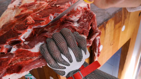 Butcher working on debone meat with safety metal gloves,industrial job 4k Live Action