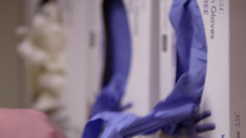 Close up view of person pullng rubber gloves out of box Live Action