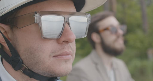Close-up portrait of confident adult male biker taking off sunglasses in slowmo Live Action
