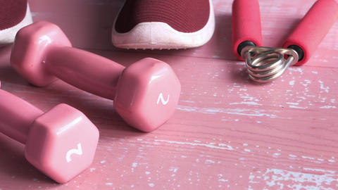 pink color dumbbell, shoe and headphone on pink background Live Action