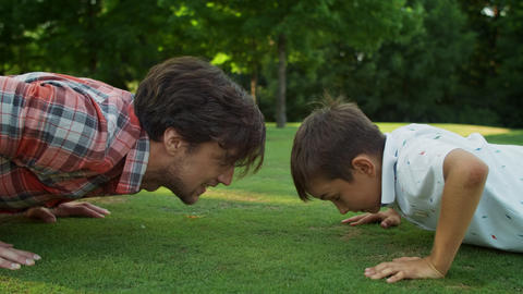 Man and boy doing push ups in meadow. Cheerful father and son training together Live Action