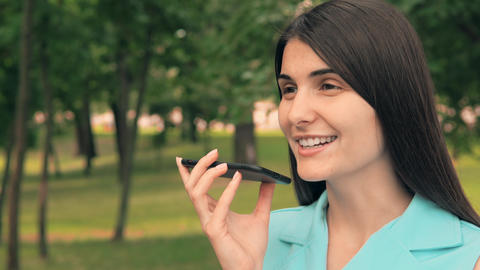 young woman dictates voice message in park Live Action