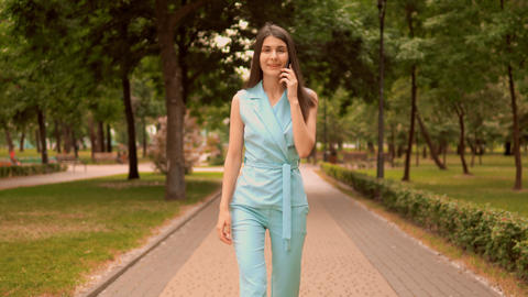 cheerful businesswoman has phone conversation on the run Live Action