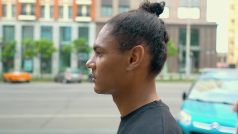 profile african american man walking along the street in city Live Action