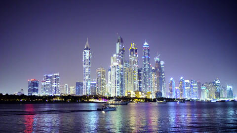 Cityscape of Night Dubai with Floating Travel Boat in the Foreground Wake Bow Waves Live Action
