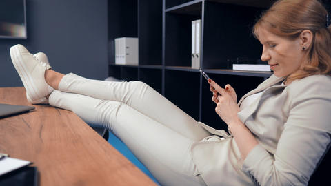 portrait adult businesswoman using mobile rest in office Live Action