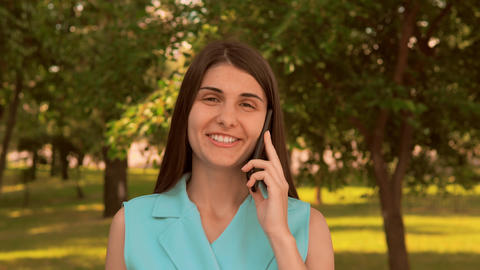 portrait cheerful young woman talking by mobile outdoors Live Action