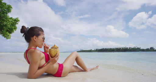 Relaxing woman sunbathing lying in sand on beach in bikini drinking from coconut Live Action