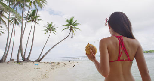 Beach vacation bikini Asian girl drinking healthy coconut water from fresh fruit Live Action
