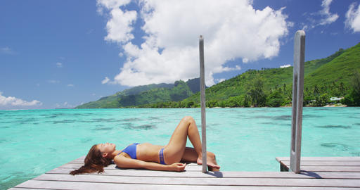 Travel luxury vacation destination bikini woman sunbathing at overwater bungalow Live Action