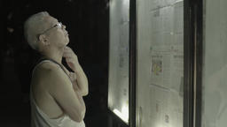 The resident reads news from Newspapers behind glass in the Park . Beijing Footage