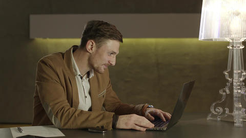 Businessman smiling while looking at the screeen of his laptop computer Footage
