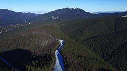 Aerial flight above forest and hills with mountain range on bg Footage