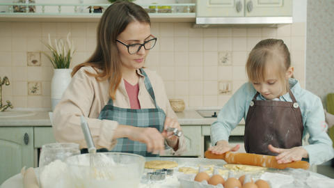 Mother and daughter baking biscuits and chatting busy with bakery indoors in Live Action