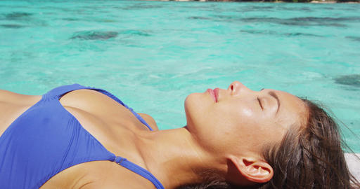 Skin care beauty and sun protection woman sun bathing by perfect turquoise water Live Action