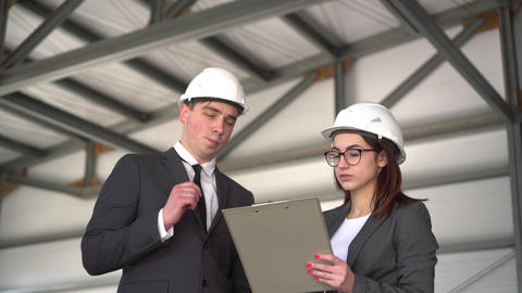 Young man and woman in helmets with documents at a construction site. Chiefs in ライブ動画