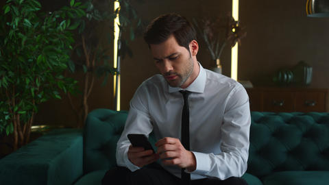 Business man typing on smartphone at office. Surprised manager using cellphone Live Action