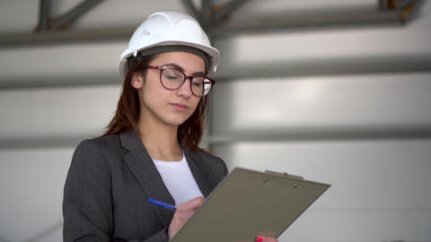 Young woman in a helmet with documents at a construction site. The boss woman in ライブ動画
