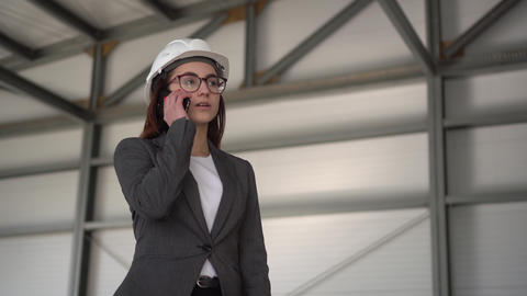 A young woman in a helmet speaks on the phone at a construction site. The boss ライブ動画