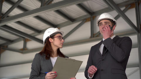 Young man and woman in helmets with documents at a construction site. Bosses in ライブ動画