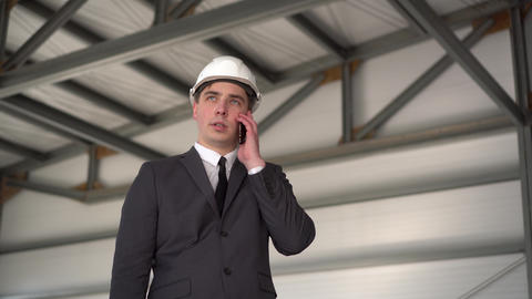 A young man in a helmet speaks on the phone at a construction site. The boss in ライブ動画