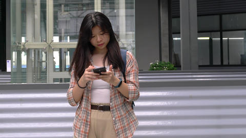 Young girl using her cellphone to message or browsing the internet Live Action
