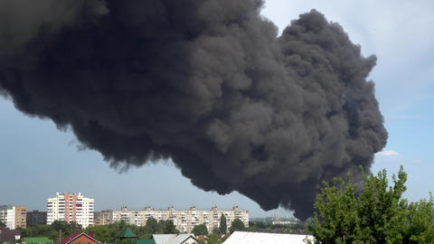 Black smoke rises above the buildings. A big chemical fire at a factory building Live Action
