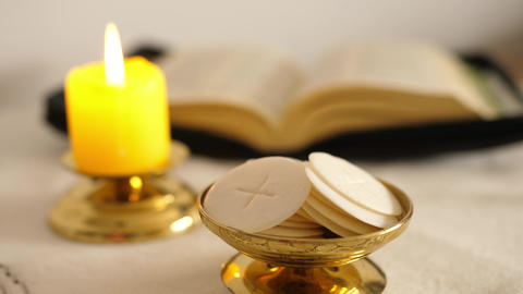 communion hosts lit candle and holy bible ライブ動画