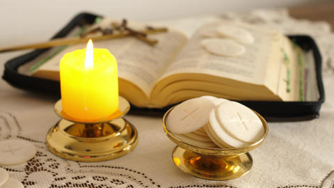 communion hosts lit candle and holy bible cross with jesus ライブ動画