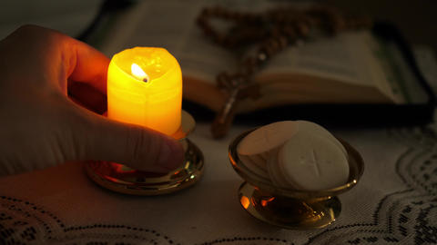 faithful puts a candle next to the communion hosts in the twilight ライブ動画