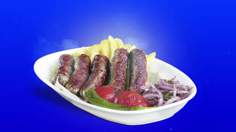 Turkish meatballs (inegol kofte) served with fried potato tomato and pepper on white plate on blue Live Action