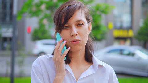 portrait caucasian woman talking by phone urban city background Live Action