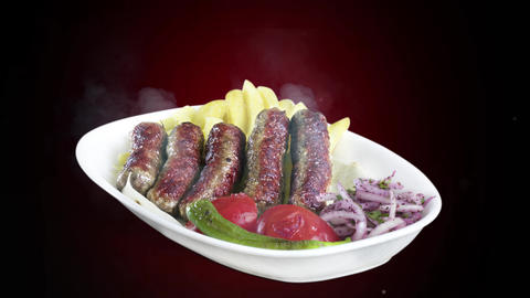 Turkish meatballs (inegol kofte) served with fried potato tomato and pepper on white plate on dark Live Action