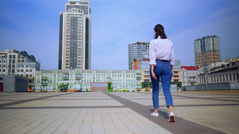 back view casual woman walks in modern city summer season Live Action