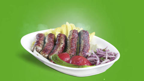 Turkish meatballs (inegol kofte) served with fried potato tomato and pepper on white plate on green Live Action
