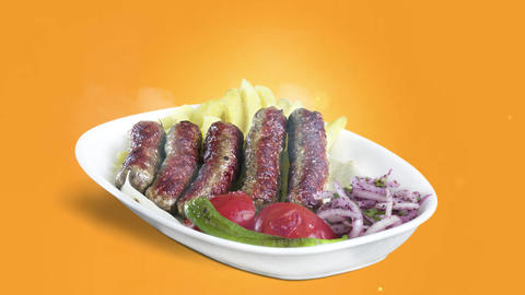Turkish Inegol Kofte served with fried potato tomato and pepper on white plate on orange background Live Action