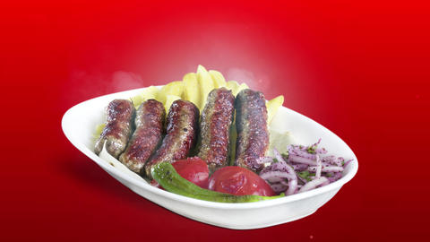 Turkish Inegol Kofte served with fried potato tomato and pepper on white plate on red background Live Action