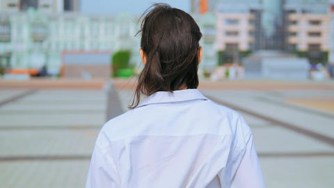 rear close up woman walks outdoors urban city background Live Action
