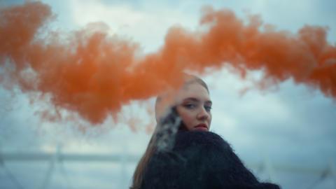 Girl waving hand at camera with smoke bomb. Young woman posing at camera Live Action