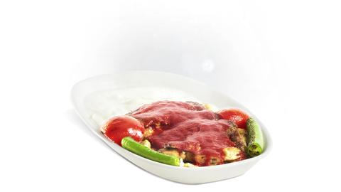 Iskender Kebab on white plate on white background direction from left to center Live Action