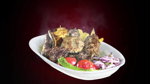 Mixed Kebab served with fried potato tomato and pepper on white plate on dark background Live Action