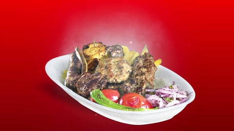 Mixed Kebab served with fried potato tomato and pepper on white plate on red background Live Action