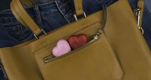 Two heart sticks out of the pocket of a female yellow bag. Rotation. Background Live Action