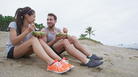 Salad - healthy lifestyle couple eating salad after fitness workout on beach Live Action