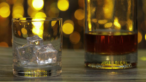 Pouring of golden whiskey, cognac or brandy from bottle into glass with ice ライブ動画
